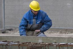 031215 GRONINGEN STAD - Geveke pleegt nieuwbouw. Wiebengacomplex. FOTO : Timmerende bouwvakker in geveke doorwerkkleding met een bouwhelm op en veiligheidsschoenen aan
